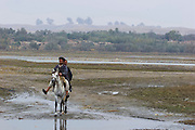 Afghan men cross the Darya river whilst B52 airstrikes pound Taliban positions in the distance.