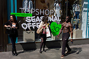 Topless black man with bulging muscles walks past women shoppers in central London.