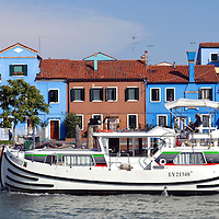 """Burano, Italy 1 July 2009<br /> A charter boat with the colourfully painted houses in the background, in Burano. More info about the charter boat: www.charterboat.it<br /> Burano is an island in the Venetian Lagoon, It lies near Torcello at the northern end of the Lagoon, and is known for its lacework.Burano is situated 7 kilometers from Venice, a short 40 minute trip by Venetian motorboats, """"vaporetti"""".<br /> The Venetian Lagoon is the enclosed bay of the Adriatic Sea in which the city of Venice is situated. Its name in the Venetian language, Laguna Veneta - cognate of Latin lacus, """"lake"""" - has provided the international name for an enclosed, shallow embayment of saltwater, a lagoon.<br /> PHOTO: EZEQUIEL SCAGNETTI"""