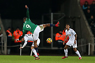 Salomon Rondon of West Bromwich Albion falls over the top of Roque Mesa of Swansea city. Premier league match, Swansea city v West Bromwich Albion at the Liberty Stadium in Swansea, South Wales on Saturday 9th December 2017.<br /> pic by  Andrew Orchard, Andrew Orchard sports photography.