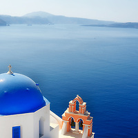 Santorini. Cyclades. Greece. View of the blue domed Anastasis Church which overlooks the azure blue waters of the caldera. The church is located in the northern picture postcard village of Oia.