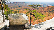 Look across miles of autumn orange and red foliage at Hanging Rock State Park, Stokes County, North Carolina, USA. The eroded quartzite knob called Hanging Rock rises to 2150 feet elevation. The park is 30 miles (48 km) north of Winston-Salem, and approximately 2 miles (3.2 km) from Danbury. Hanging Rock State Park is located in the Sauratown Mountain Range, which is made up of monadnocks (or inselbergs, isolated hills) that are separated from the nearby Blue Ridge Mountains. Prominent peaks in the Sauratown range rise from 1,700 feet (520 m) to more than 2,500 feet (760 m) in elevation and stand in contrast to the surrounding countryside, which averages only 800 feet (240 m) in elevation. Named for the Saura Native Americans who were early inhabitants of the region, the Sauratown Mountains are the erosion-resistant quartzite remnants of mountains pushed up between 250 and 500 million years ago. Panorama stitched from 2 overlapping photos.