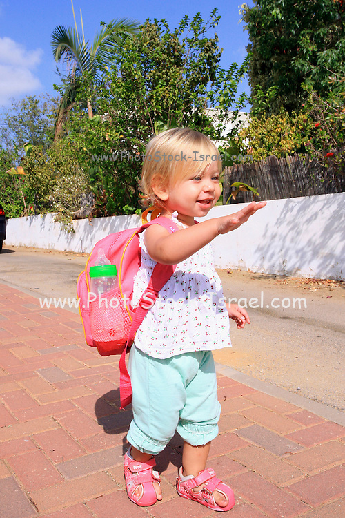 A 18 month toddler girl, with a small lunch pack with bottle ready for kindergarten waving bye-bye