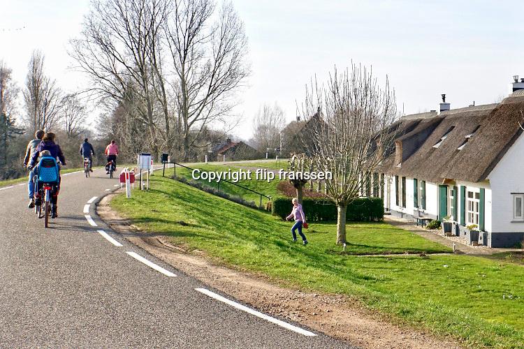 Nederland,Ooijpolder, 17-2-2019 Mensen, ouderen, maken een fietstochtje over de dijk langs de Waal, Rijn . Het is een mooie dag met zon en een blauwe onbewolkte lucht. FOTO: FLIP FRANSSEN
