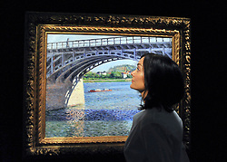 © Licensed to London News Pictures. 07/10/2011. LONDON. UK. A Sotheby's worker looks at Gustave Caillebotte's Le Pont d'Argenteuil et la Seine  at a Sotheby's Preview.  The piece will be sold at auction in October 2011 and is expected to fetch $9/12million. Photo credit:  Stephen Simpson/LNP