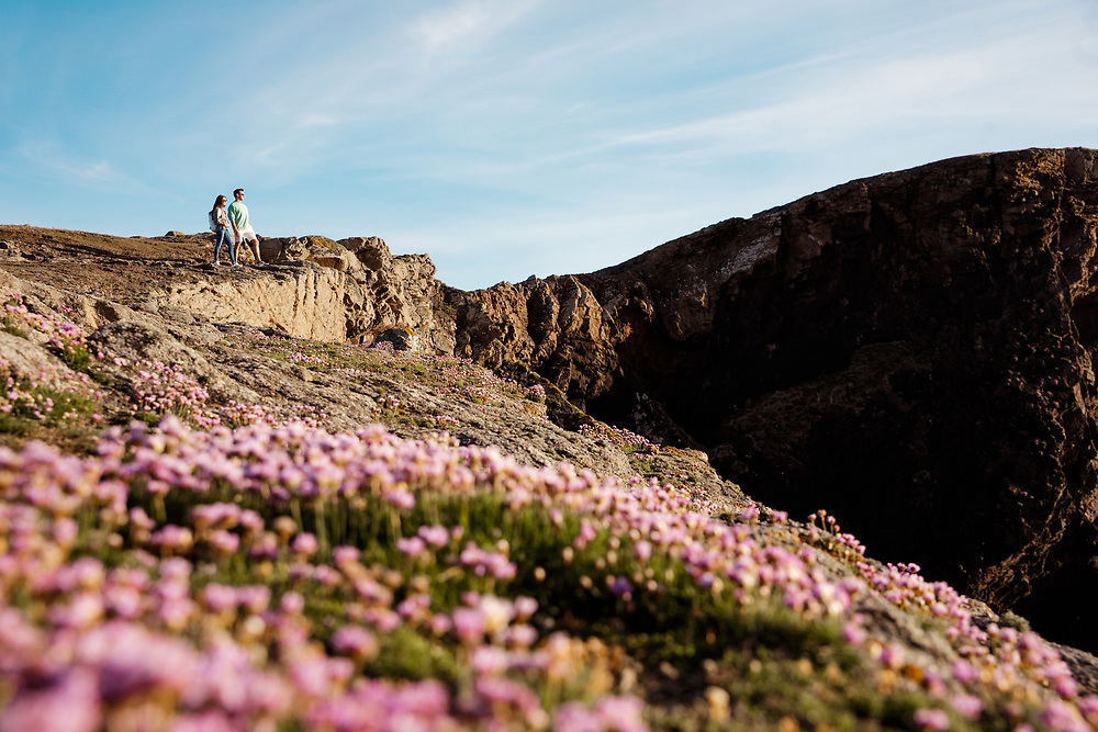 Couple adventuring and walking on the cliff paths, enjoying a healthy active lifestyle on a sunny day in Spring in Jersey, Channel Islands