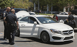June 26, 2017 - Anaheim, CA, USA - Police investigate a stolen white Mercedes in their department parking lot after a pursuit and arrest a man driving in Anaheim, CA on Monday, June 26, 2017. The vehicle theft suspect called 911 during the pursuit to inform police he would be driving to the police station. (Credit Image: © Ken Steinhardt/The Orange County Register via ZUMA Wire)