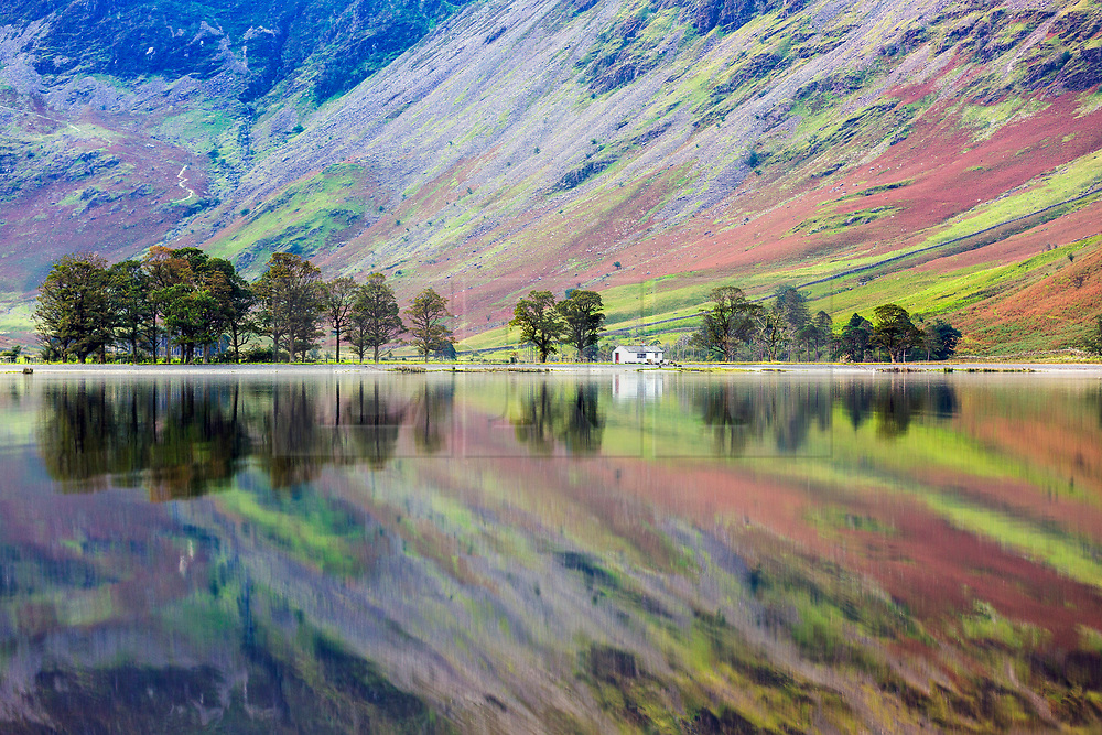 © Licensed to London News Pictures. 15/09/2020. Buttermere UK. The Little White hut & low laying land of Haystacks mountain reflect into the still water of Buttermere lake in Cumbria this morning. Photo credit: Andrew McCaren/LNP