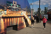 Lady joggers run past CCTV a camera and a construction hoarding, a night time panorama of the Thames south bank, featuring the HQ of the intelligence service (MI6) across the river in Vauxhall.