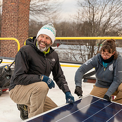 PV Squared employees installing solar panels on the roof of a commercial building in Greenfield, Massachusetts.
