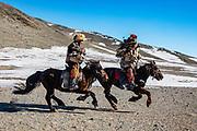 Kazakh eagle hunters with their golden eagles (Aquila chrysaetos) galloping on horseback , Altai Mountains, Bayan Ulgii, Mongolia