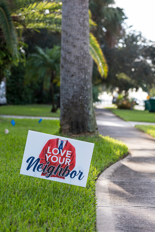 """Stuck into the green grass of a residential yard, a sign reading """"Love Your Neighbor"""" features Mr. Rogers' famous red sweater. (Indialantic, Florida - November 3, 2020)"""