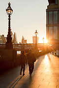 Man and woman walking along Southbank at sunrise, London, England, UK
