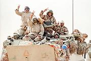 Saudi Arabian soldiers flash the victory sign during clean up operations following the Battle of Khafji February 2, 1991 in Khafji City, Saudi Arabia. The Battle of Khafji was the first major ground engagement of the Gulf War.