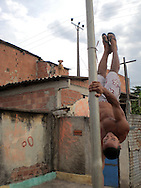 Bebel on a pole Vigário Geral 2006.<br /> Roberto Bebel Monteiro Guimares 1983-2007 In 2006 Bebel was 23 he became a close friend of mine because we worked closely together in two different places. He liked practicing his English with me. He was a thoughtful funny and proud man. His family had suffered a lot of loss and he had overcome a lot of challenges to stay out of the drug traffic look after his family and excel at circus arts. His mother died when he were young and his younger brother Nanao who had been caught up in the drug traffic was tortured and killed by police in 2005. Sadly Bebel died in 2007 from an illness not gunfire. This project is dedicated to him. <br /> Part of the series Viver no Meio do Barulho (Living in the Middle of the Noise)