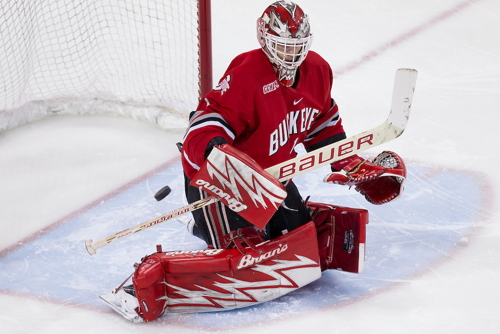 Ohio State goaltender Cal Heeter (#1) makes the save in second period action of NCAA hockey game between Notre Dame and Ohio State.  The Notre Dame Fighting Irish defeated the Ohio State Buckeyes 4-2 in game at the Compton Family Ice Arena in South Bend, Indiana.