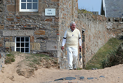 Embargoed to 0001 Monday August 28 A batsman walks to the ground during a match between the Ship Inn Cricket Club and the Eccentric Flamingoes Cricket Club on Sunday April 30th, 2017, in front of the pub in Elie, Fife, which is the only one in Britain to have a cricket team with a pitch on the beach. The Ship Inn Cricket Club season runs from May to September with dates of matches dependent on the tides. Any Batsman who hits a six which lands in the Ship Inn beer garden wins their height in beer and any spectator who catches a six in the beer garden also wins their height in beer.