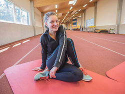 Young woman doing floor exercise in athletics hall on tartan track, Offenburg, Baden-Wuerttemberg, Germany