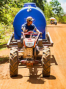 02 JUNE 2016 - SIEM REAP, CAMBODIA:  NGOR, 33 years old, drives his tractor with a 3,000 litre water tank on it while he sells water from his well in the villages around his home east of Siem Reap. Cambodia is in the second year of  a record shattering drought, brought on by climate change and the El Niño weather pattern. Farmers in the area say this is driest they have ever seen their fields. They said they are planting because they have no choice but if they rainy season doesn't come, or if it's like last year's very short rainy season they will lose their crops. Many of the wells in the area have run dry and people are being forced to buy water to meet their domestic needs.   PHOTO BY JACK KURTZ