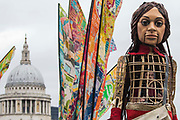 Little Amal, a giant puppet of a Syrian refugee girl fleeing conflict, crosses the Millennium Bridge en route from St Pauls Cathedral to the Globe Theatre on 23rd October 2021 in London, United Kingdom. The 3.5-metre puppet, which is nearing the end of an 8,000km journey from the Turkish-Syrian border to Manchester in support of refugees, climbed the steps of St Pauls Cathedral to present a wood carving of a ship at sea from St Pauls birthplace at Tarsus in Turkey to the dean.