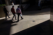 Three associates walk through area of City of London sunlight with takeaway lunch bags. Making their way through from dark shadow into the pool of urban light, the men are in step with each other - all striding and carrying the sandwich bags bought locally. The architecture and cityscape is in the capital's financial heart - the City of London, known as the Square Mile, founded by the Romans in AD43.
