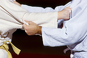 Detail of the hands of judo competitors in action.