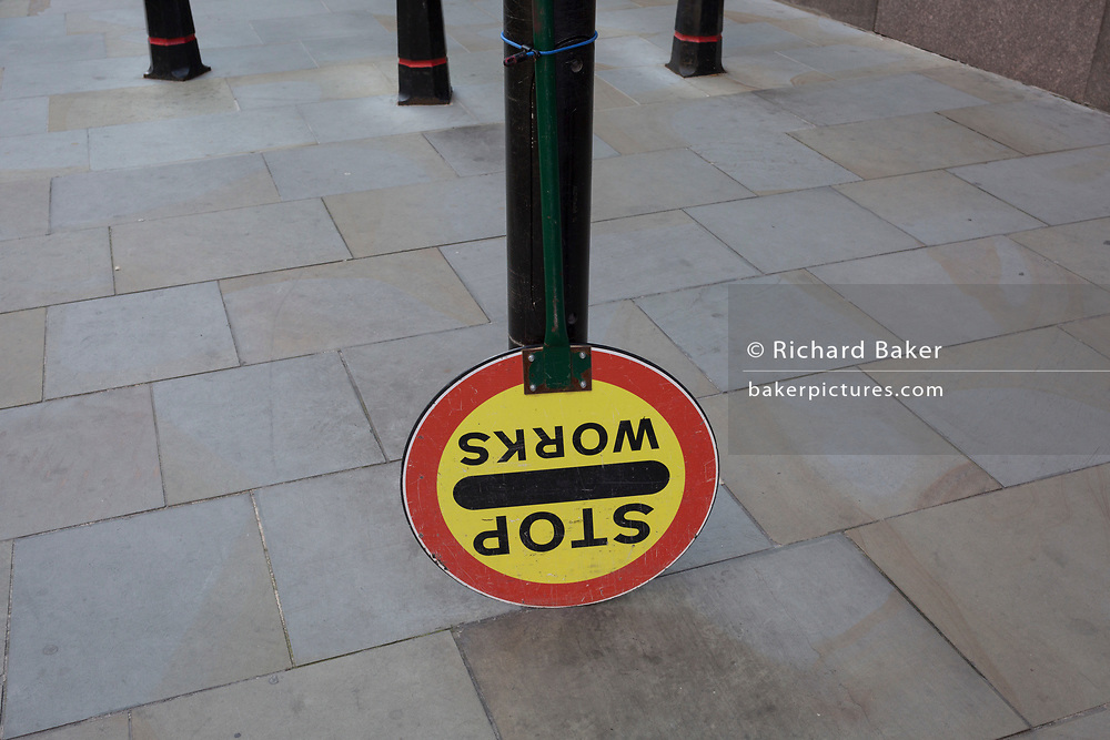 A building site Banksman's lollipop sign that usually tells road-users to allow for turning construction traffic, is tied upside down on to a post in the street on Sun Street near Liverpool Street Station in the City of London, the capital's financial district - aka the Square Mile, on 8th August, in London, England.