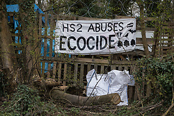 Wendover, UK. 9th April, 2021. A banner accusing HS2 Ltd of ecocide hangs outside the Wendover Active Resistance Camp on 9th April 2021 in Wendover, United Kingdom. Tree felling work for the project is now taking place at several locations between Great Missenden and Wendover in the Chilterns AONB, including opposite the camp and at Jones Hill Wood.