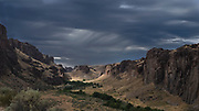 A late afternoon thunderstorm arrives in the lower Owyhee River area of southeastern Oregon casting beautiful light on this high desert region.