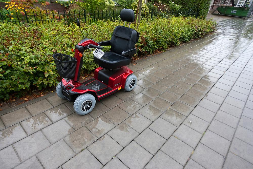 Een scootmobiel staat in de regen.<br /> <br /> A scooter in the rain