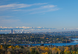 North America, United States, Washington. Lake Washington, Mercer Island, Seattle skyline, and Olympic mountains viewed from Bellevue in autumn.