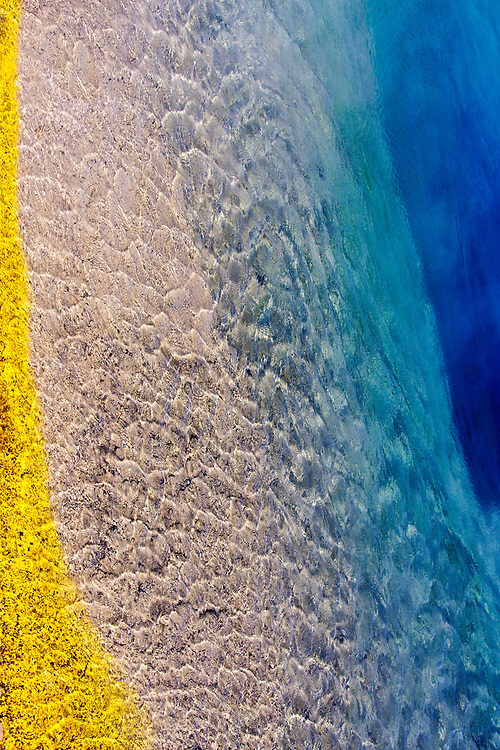 a colorful blend of yellow, aqua, blue, and clear waters due to the microorganisms on the surface of the earth of a hot spring at yellowstone national park