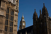 The tower containing Big Ben amid the Gothic architecture of Britain's Houses of Parliament. To the left we see the Gothic Revival facade of Westminster Abbey's Henry the VIII's Lady Chapel that juts out on the eastern side towards the Palace of Westminster or The House of Commons, which is the lower house of the Parliament of the United Kingdom, which also comprises the Sovereign and the House of Lords (the upper house). Both Commons and Lords meet in the Palace of Westminster.