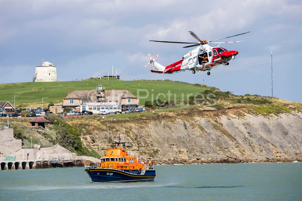 The Royal National Lifeboat Institution RNLI Dover Life boat 17-09 and HM Coastguard rescue helicopter G-C1JW take part in a training exercise in front of the white cliffs outside Folkestone Harbour, Folkestone, Kent. UK. 6th August 2016