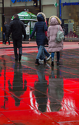 The lights from the famous advertising billboards of Piccadilly Circus are reflected in the wet pavements. As forecasters predicted, the rain arrives in London where Londoners and tourists go about their business. London, February 13 2018.