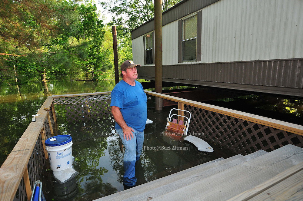 """8/11/11} Vicksburg} -- Vicksburg, MS, U.S.A. -- Mark Bridges,56, thrift store owner, stands in what was his side porch and surveys the damage to his neighborhood. Mark and his dog """"baby girl"""" and his girlfriend of 12 years Patricia Clark, a homeDepot garden employee, cruise down Chicksaw Rd in a bass boat in North Kings Community in Vicksburg Mississippi Wed. May 5th 2011. This is the firs time for Patricia to try and remove things from her trailer, that is built on 9ft stilts  AND THE WATER IS CURRENTLY AT 15 ft. and rising and is less than 12 inches from being flooded. Mark and Patricia have lived their all their lives and will return when the Mississippi River recedes,. ark has been helping his neighbors get their belongings to safety. Vicksburg a riverfront town steeped in war and sacrifice, gets set to battle an age-old companion: the Mississippi River. The city that fell to Ulysses S. Grant and the Union Army after a painful siege in 1863 is marshalling a modern flood-control arsenal to keep the swollen Mississippi from overwhelming its defenses. PHOTO©SUZIALTMAN.COM.Photo by Suzi Altman, Freelance."""