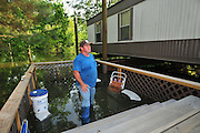 "8/11/11} Vicksburg} -- Vicksburg, MS, U.S.A. -- Mark Bridges,56, thrift store owner, stands in what was his side porch and surveys the damage to his neighborhood. Mark and his dog ""baby girl"" and his girlfriend of 12 years Patricia Clark, a homeDepot garden employee, cruise down Chicksaw Rd in a bass boat in North Kings Community in Vicksburg Mississippi Wed. May 5th 2011. This is the firs time for Patricia to try and remove things from her trailer, that is built on 9ft stilts  AND THE WATER IS CURRENTLY AT 15 ft. and rising and is less than 12 inches from being flooded. Mark and Patricia have lived their all their lives and will return when the Mississippi River recedes,. ark has been helping his neighbors get their belongings to safety. Vicksburg a riverfront town steeped in war and sacrifice, gets set to battle an age-old companion: the Mississippi River. The city that fell to Ulysses S. Grant and the Union Army after a painful siege in 1863 is marshalling a modern flood-control arsenal to keep the swollen Mississippi from overwhelming its defenses. PHOTO©SUZIALTMAN.COM.Photo by Suzi Altman, Freelance."