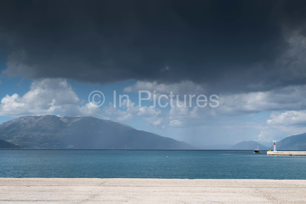 Storm clouds over the port of Sami. Kefalonia, Greece. The port of Sami, Kefalonia, Greece. The village reaches a population of 1000 inhabitants most of whom are engaged in agriculture and fishing. Sami is the second largest port of Kefalonia after Argostoli and it serves daily trips to Patra, Ithaca and Italy. The modern village is built close to ancient Sami, one of the most important archeological discoveries of Kefalonia.
