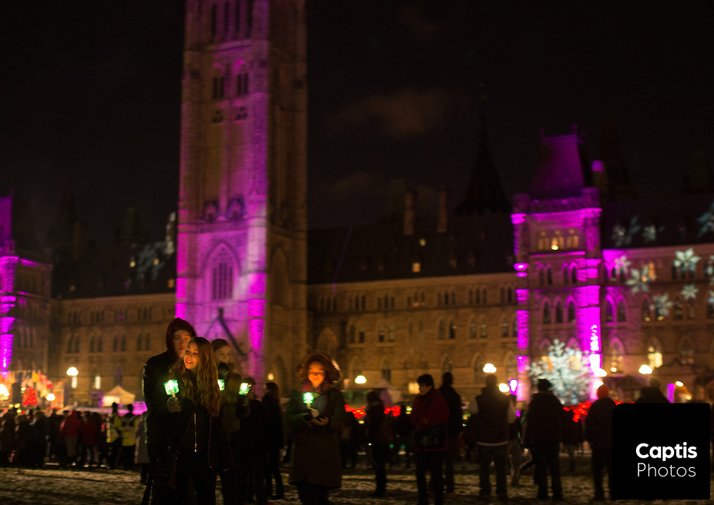 People holding candles walk away from the Parliament Buildings following the opening ceremony for holiday lights on the Hill. December 3, 2014.