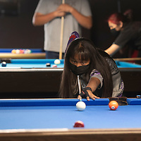 Asia Gillespie, 10, practices pool Tuesday evening at Q & A Billiards in Gallup. She is learning competitive billiards from Gina Kim, the owner of Q&A Billiards.