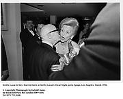 Swifty Lazaar & Mrs. Marvin Davis at Swifty Lazar's Oscar Night party. Spago. Los Angeles. March 1990.<br /><br />© Copyright Photograph by Dafydd Jones<br />66 Stockwell Park Rd. London SW9 0DA<br />Tel 0171 733 0108<br />Film. 90232/13