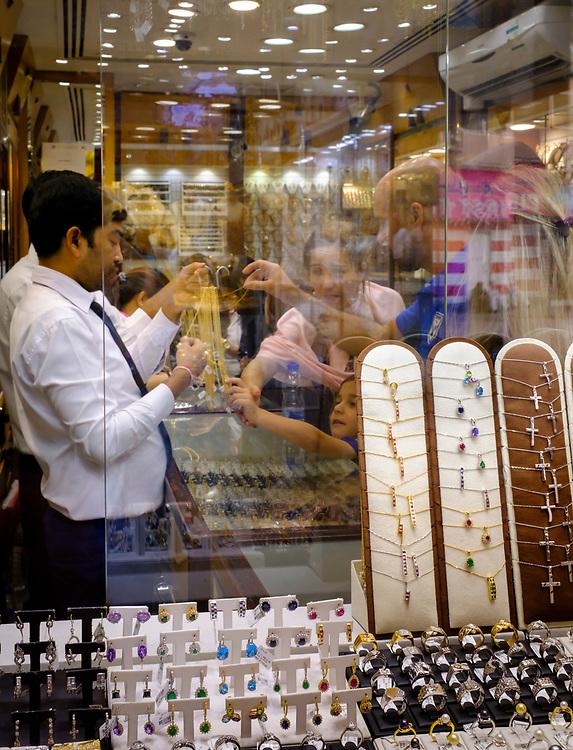 UNITED ARAB EMIRATES, DUBAI - CIRCA JANUARY 2017: Tourists shopping for jewelry at the famous Gold Souq in Dubai