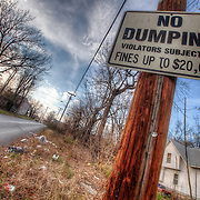 People look for a No Dumping Sign to drop off their trash.