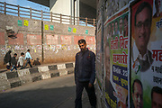 A man walks through an underpass surrounded by political posters in New Delhi, India