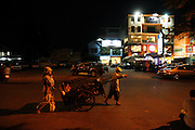 A family of recycling workers trudge through the city streets at night in search of recyclable materials, Phnom Penh. Rural peasants who have left the countryside in search of earning a decent living often end up as recycling workers on Phnom Penh's city streets. They earn a few dollars a day from selling by weight the plastic bottles, aluminium cans and cardboard they collect during a days work. Usually they work from the mid afternoon until midnight, sorting through the rubbish on the streets. They take what they collect to small sorting houses on the edge of the city.