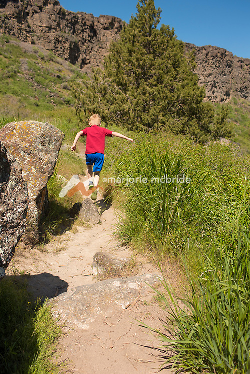 Little boy leaping over a rock while hiking with family in Box Canyon State Park in Wendell, Idaho. MR