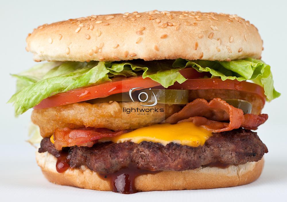 Photo of the Western Burger served at Dezereta Inc. in southern Utah area. Western burger contains, hamburger, BBQ sauce, hamburger, cheese, onion rings, bacon, lettuce, tomato, buns.