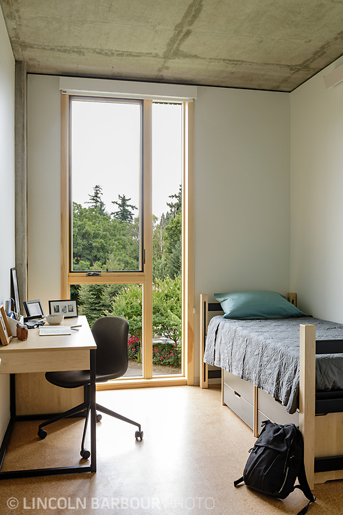 A detail of a dorm room showing the desk, bed and floor to ceiling windows.