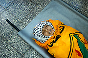 Wrapped in the flag of the Al Aqsa Martyrs' Brigade, he body of Mona Abu Tabak, 9, is laid on the stretcher of a hospital in Gaza. The hospital staff said Tabak was shot in the stomach by an Israeli sniper when she was going to a shop.