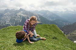 Young girl and boy playing wrestling on grass Alps